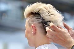 POZNAN POLEN - MAJ 07 2016: Frisör som ordnar frisyren på T Royaltyfri Bild