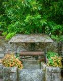 Pozo antiguo rodeado por las flores coloridas en Rochefort-en-Terre, Bretaña francesa imagen de archivo libre de regalías