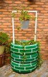 pozo de agua urbano que adorna un jardín urbano con los neumáticos pintados, un cubo gris con las plantas en un fondo del ladrill foto de archivo libre de regalías