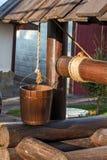 Pozo de madera. Cubo en una cuerda Fotografía de archivo libre de regalías