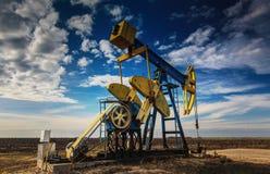 Pozo de petróleo de funcionamiento perfilado en el cielo nublado dramático Imagen de archivo