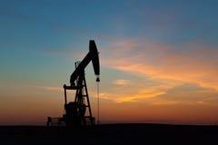 Pozo de petróleo silueteado contra puesta del sol de la pradera Fotos de archivo
