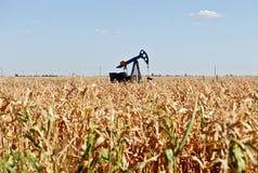 Pozo de petróleo y campo de maíz Foto de archivo