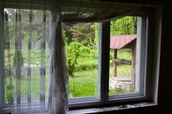Pozo viejo visto a través una ventana rústica imagenes de archivo