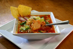 Pozole Rojo Mexican Soup. Classic, traditional Mexican stew with pork, chicken, hominy, red chilis, onions, garlic and oregano.  Topped with fresh lettuce, lime Royalty Free Stock Photography
