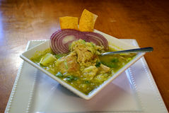 Pozole Verde Soup. Classic Mexican stew with pork, chicken and sausage and green tomatillo chilis.  Topped with fresh lettuce, lime wedge, red onion and tortilla Stock Images