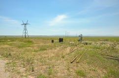 Pozos de petróleo ilegal y una línea de transmisión en un campo Imagen de archivo