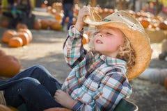 Pozować Little Boy w kowbojskim kapeluszu przy Dyniową łatą Zdjęcie Royalty Free