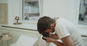 Pozujący pozytywnej dziewczyny dla jej chłopaka który robi niektóre obrazkom w łóżku, w ranku mieć niektóre wspominki, wygodnych zdjęcie wideo
