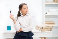 pozwól mi pomyśleć Dziecko dziewczyna jest ubranym mundurek szkolny pozycję z pamiętać twarzy wyrażenie Uczennicy dziecka mądrze  obrazy stock