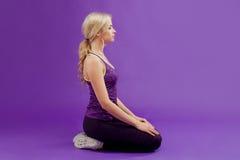 pozy joga Młode sporty kobiety na purpurowym tle Relaksuje, siedzi, z ukosa obrazy royalty free
