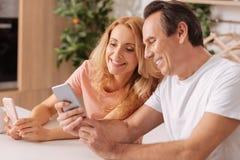 Pozytyw dojrzała para używa cyfrowych smartphones w domu obraz stock