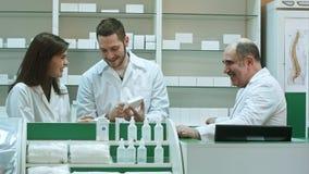Pozytyw drużyna farmaceuty patrzeje pudełko pastylka przy szpitalną apteką Obrazy Stock