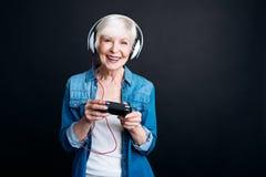 Pozytyw starzejąca się kobieta bawić się wideo gry Fotografia Stock