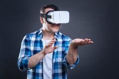Pozytyw zachwycał mężczyzna ma wirtualnego przedmiot w jego ręce Zdjęcie Stock