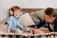 Pozytyw zachwycający mężczyzna dziecko słucha muzyka obraz royalty free