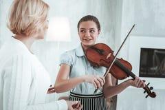 Pozytywna ładna dziewczyna patrzeje jej muzycznego nauczyciela obrazy stock