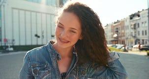 Pozytywna ładna dziewczyna z brasami trząść jej ciemnego kędzierzawego włosy plenerowego 4k materiał filmowy zdjęcie wideo