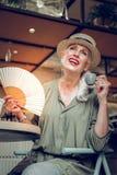 Pozytywna ładna kobieta używa pięknego fan zdjęcie stock