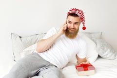 Pozytywna atrakcyjna brodata samiec z gęstą brodą ubierającą w przypadkowym domowym odzieżowego i Santa s kapeluszu, przyjemnego fotografia royalty free