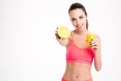 Pozytywna attrative młoda sportsmenka pokazuje pomarańczową połówkę zdjęcia stock