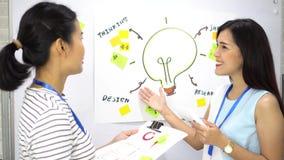 Pozytywna azjatycka przedsiębiorca prezentuje koleżankę zbiory