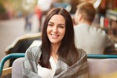 Pozytywna brunetki kobieta z jaśnienie uśmiechem, wydaje czas wolnego w dobrej firmie przy restauracją, zawijającą w ciepłej szko Fotografia Royalty Free