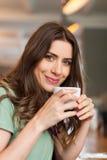 Pozytywna dziewczyna bierze przerwy obsiadanie przy barem w cukiernianym sklepie zdjęcia stock