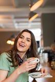Pozytywna dziewczyna bierze przerwy obsiadanie przy barem w cukiernianym sklepie zdjęcia royalty free