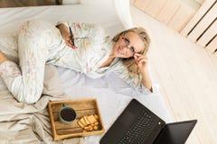 Pozytywna młoda kobieta sprawdza poczta na smartphone w ranku lying on the beach w łóżku pokój hotelowy z laptopem, kobieta Obraz Royalty Free
