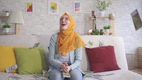 Pozytywna młoda Muzułmańska kobieta siedzi na kanapie w domu łapie spada banknoty zbiory wideo
