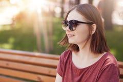 Pozytywna młoda urocza kobieta z modną fryzurą, jest ubranym modnych cienie, siedzi na ławce w parku, cieszy się pogodną pogodę p fotografia stock