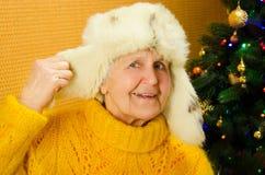 Pozytywna starsza kobieta wyraża szczęście w wakacje Portret szczęśliwa babcia nad dekorującym nowego roku drzewem obraz royalty free