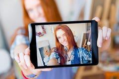 Pozytywna uśmiechnięta kobieta robi selfie używać pastylkę w artysty warsztacie Zdjęcia Stock