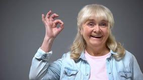 Pozytywna uśmiechnięta starzenie się kobieta pokazuje ok gest, rządowy pomocy zatwierdzenie fotografia stock