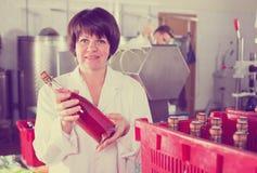 Pozytywne żeńskie pracownika kocowania wina butelki Obrazy Stock
