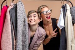 Pozytywne atrakcyjne kobiety wybierają odziewają w centrum handlowym zdjęcie stock