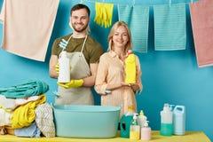 Pozytywne dobre przyglądające pary mienia detergentu butelki zdjęcia stock