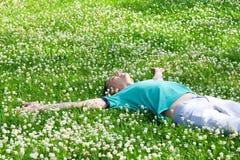Pozytywne mężczyzna lying on the beach ręki szeroko rozpościerać na zielonej lato łące Zdjęcia Stock