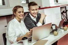 Pozytywni młodzi pracownicy wydaje czas w biurze podczas gdy rozdający z znacząco projektem zdjęcie stock