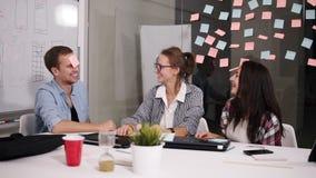 Pozytywni młodzi ludzie śmia się podczas gdy pracujący wpólnie podczas brainstorming siedzieć behind przy dużym białym biuro stoł zbiory