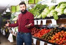 Pozytywni męscy sprzedawca ofiary pomidory w sklepie Zdjęcie Royalty Free
