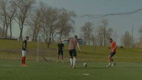 Pozytywni nastolatkowie bawić się piłkę nożną na sporta polu zbiory