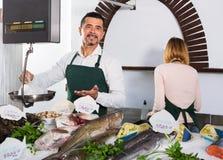 Pozytywni ono uśmiecha się rozochoceni sklepowi asystenci sprzedaje świeżej ryba zdjęcia stock