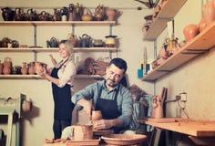 Pozytywni rzemieślnicy z ceramicznym kołem i różnorodnymi glinianymi naczyniami Zdjęcia Stock