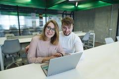 Pozytywni urzędnicy siedzą przy stołem blisko laptopu, patrzeją uśmiech i kamerę obrazy stock