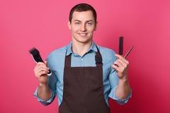 Pozytywny życzliwy przyglądający fryzjer męski z elektryczną żyletką nożyce i grępla, ubierał w koszula i fartuchu gotowych robić zdjęcie royalty free
