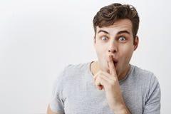 Pozytywny śmieszny mężczyzna utrzymań pierwszego planu palec na usta, przedstawienie ciszy znak z strzelającymi oczami, pyta ludz zdjęcie royalty free