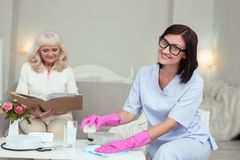 Pozytywny żeński opiekun usuwa pył zdjęcie stock