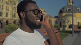 Pozytywny amerykanina afrykańskiego pochodzenia facet opowiada na telefonie w parku zdjęcie wideo
